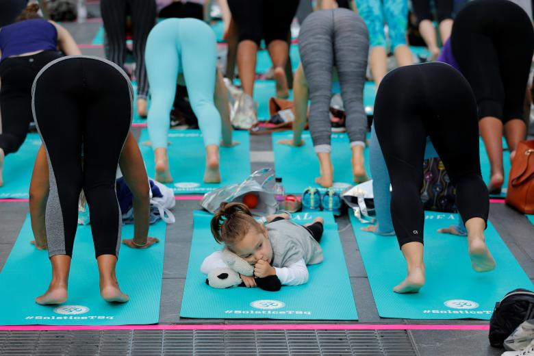 A young girl sucks her thumb as people participate in a yoga class during an annual Solstice event in Times Square. REUTERS/Lucas Jackson