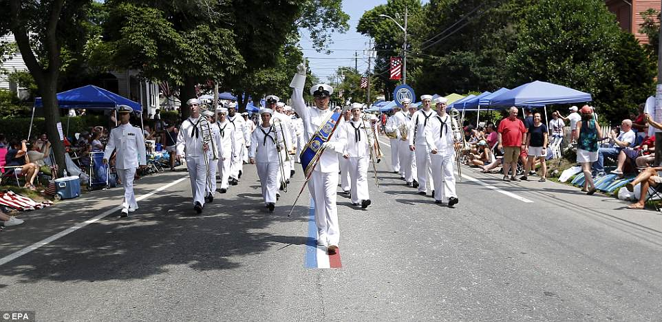 Crowds lined the streets in a Rhode Island town to see what's billed as the nation's oldest continuous Fourth of July celebration. Pictured Is the US Naval Band as they marched down Hope Street on Wednesday