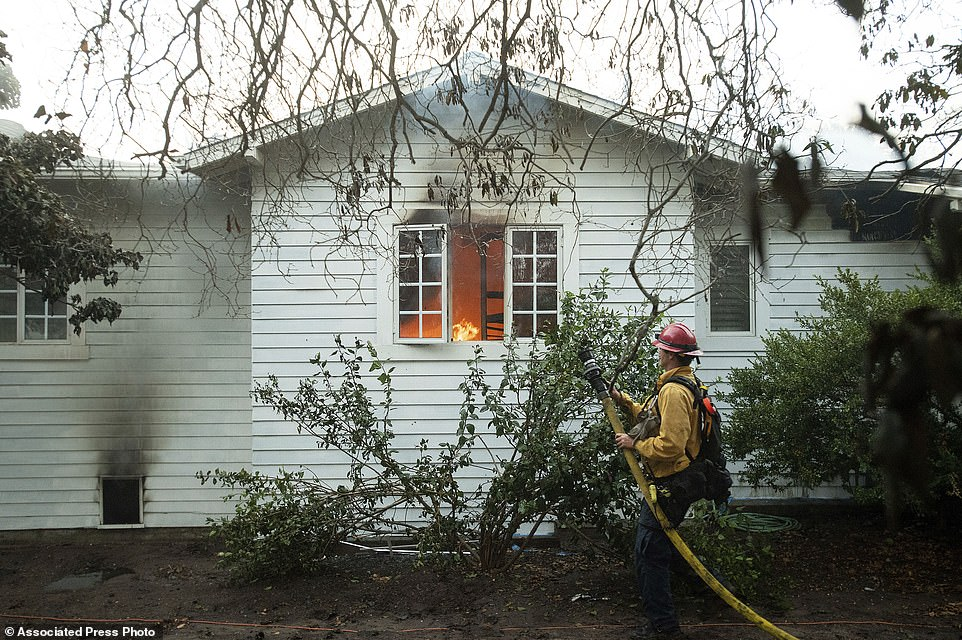 A firefighter battling the Holiday prepares to douse a burning residence in Goleta