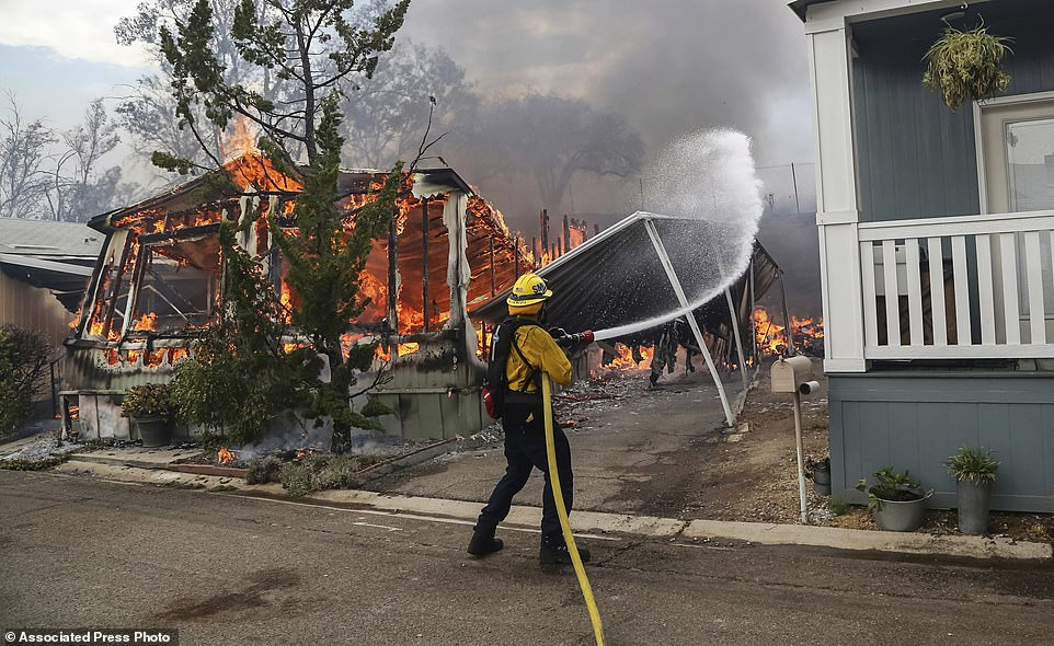 Firefighters battle flames at the Alpine Oaks Estates mobile home park during a wildfire Friday in Alpine, california