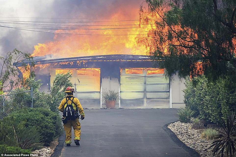 A firefighter approaches a burning home along Olive View Road. Dozens of fires are burning across the dry American West, fueled by rising temperatures and gusty winds that were expected to last through the weekend