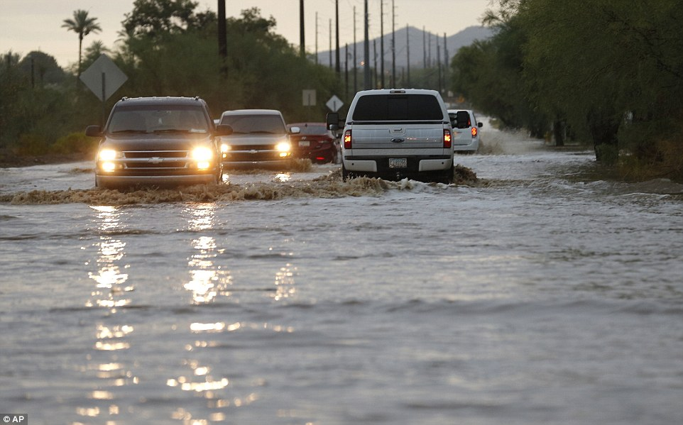 Vehicles navigate a flooded street due to severe monsoon storms moving through the metro area in Phoenix
