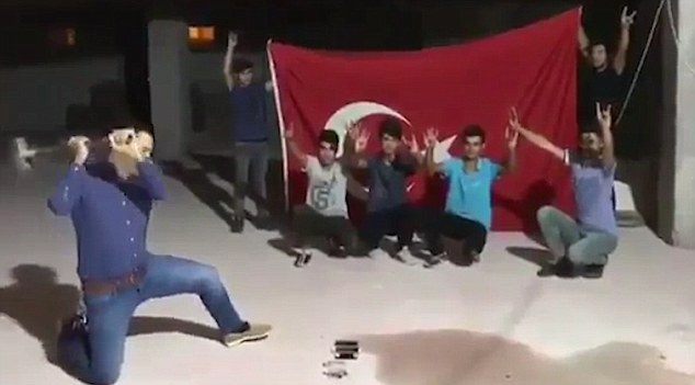 In one video, a man addresses the camera while four boys kneel in front of a Turkish flag in the background, then hand him their phones so he can smash them