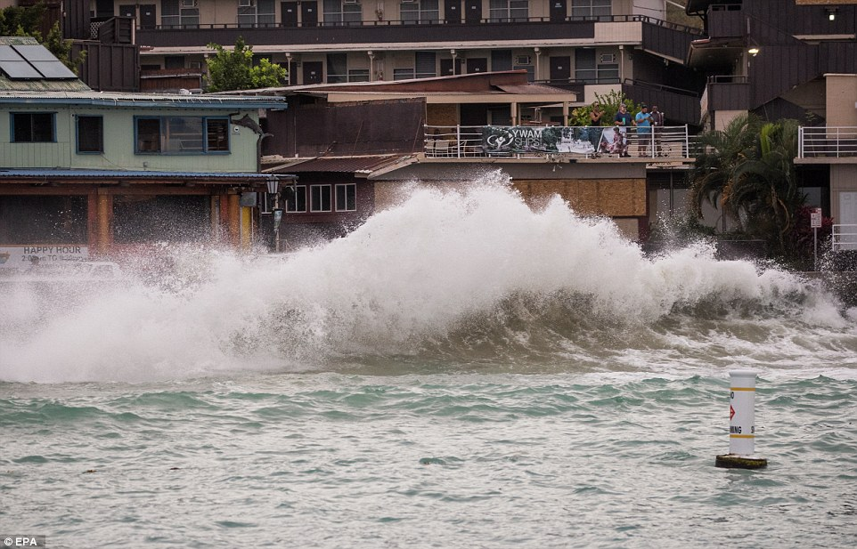 The Big Island Is being pummeled by gusty winds and torrential rains on Thursday. Pictured:rIsing surf generated by Hurricane Lane crashes upon the Kailua Kona coastline