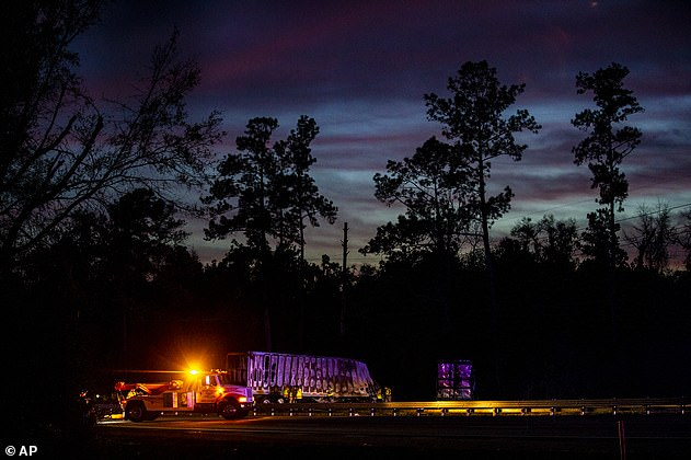 The sun sets over burned semi-trucks and vehicle debris after a wreck with multiple fatalities on Interstate 75, south of Alachua, near Gainesville