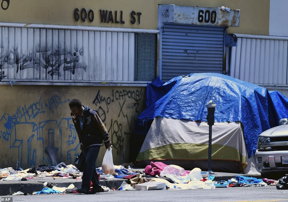 The police union says homeless encampments must be cleaned up following the recent diagnosis and other cases where officers contracted hepatitis A and staph infections.A homeless man is pictured walking along a street lined with trash across the street from LAPD Central Community Police Station in downtown Los Angeles