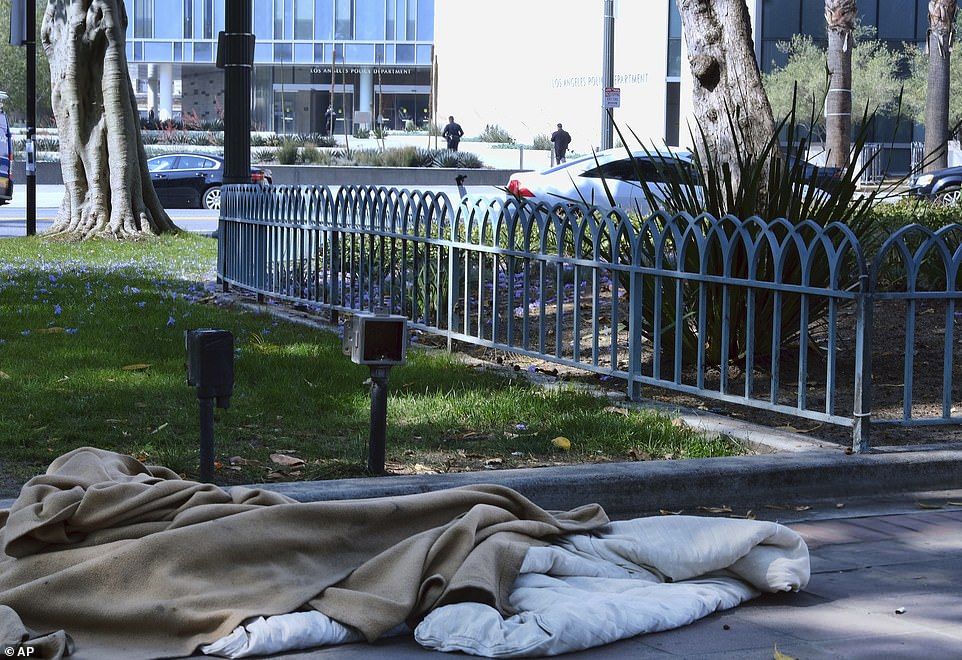 An abandoned sleeping bag and blanket is left in on the grounds of Los Angeles City Hallacross the street from Los Angeles Police Department headquarters