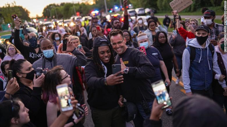 Johnie Franklin of Flint takes a selfie with Genesee County Sheriff Chris Swanson as he marches with protesters against police brutality and in memory of George Floyd on Saturday in Flint Township, Michigan.