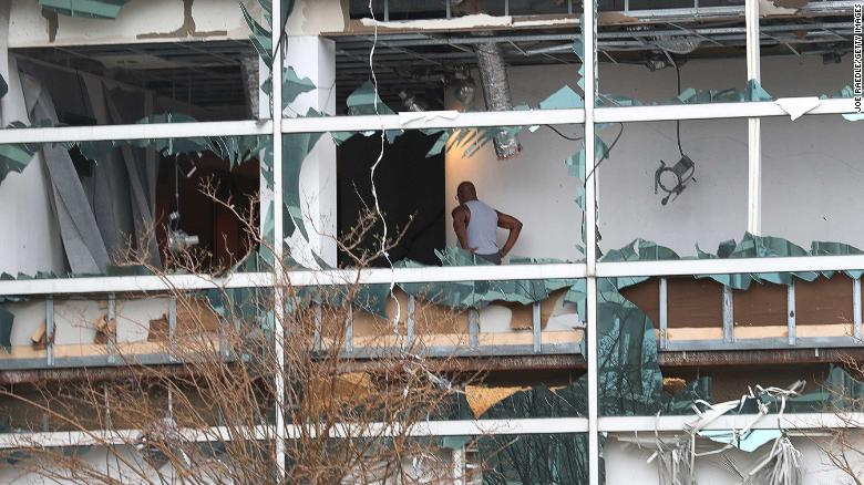 A person is seen through the blown out windows of the Capitol One Bank Tower in the downtown area of Lake Charles on Thursday.